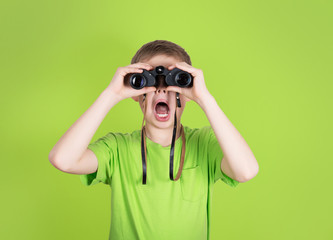 Surprised young boy with binoculars on green background.