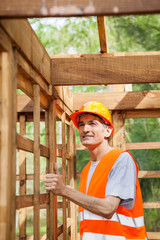 Construction Worker Standing In Incomplete Wooden Cabin