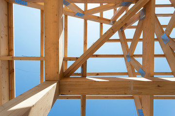 Wooden construction home framing against a blue sky