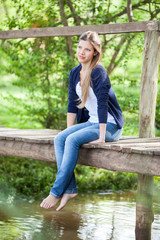 Beautiful Woman Sitting On Wooden Bridge