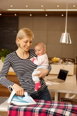 Happy mother and baby ironing