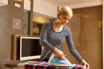 Young woman ironing at home