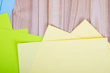 different colored paper on wooden background