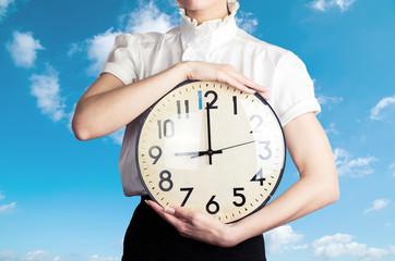 Business woman holding a clock on the sky backround