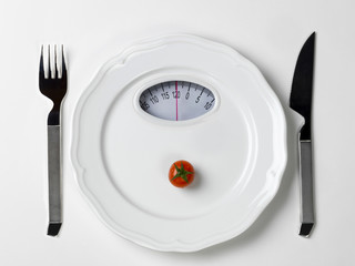 Dish with a tomato and a dial of a bathroom scale