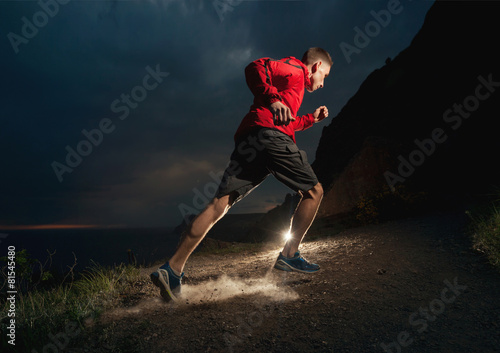 Man running in the mountains at night. - 81545480
