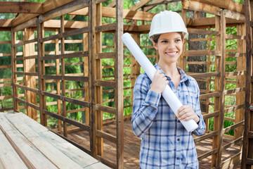 Happy Engineer Holding Blueprint In Wooden Cabin