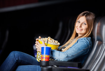 Smiling Woman With Snacks At Movie Theater