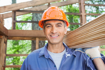 Happy Construction Worker Carrying Wooden Planks
