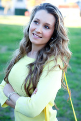 Pretty blonde girl dressed in yellow smiling