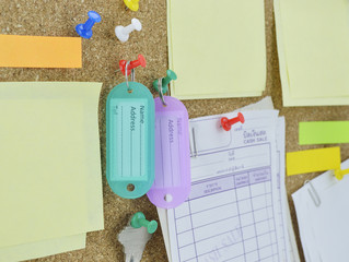 tag name, colorful sticky notes and key on cork board