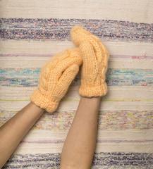female hands in woolen knitted mittens