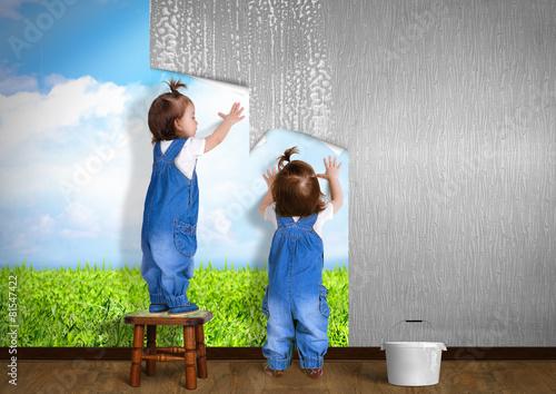 Fototapeta Little twins doing repair at home, hanging wallpaper