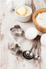 flour, measuring spoons, cookie cutters and baking ingredients