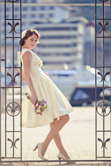Woman white retro dress standing  gate with bouquet flowers.