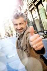 Handsome mature man showing thumb up