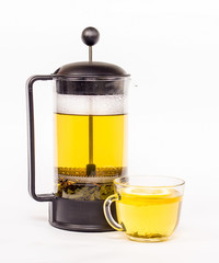 Transparent tea kettle and cup of tea with yellow tea