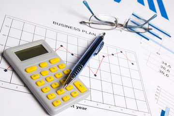 business plan concept - graphs, charts, pen, glasses and calcula