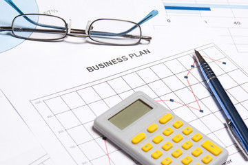 business plan concept - graphs, charts, pen and calculator
