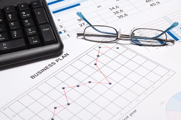 business plan concept - graphs, charts, glasses and keyboard