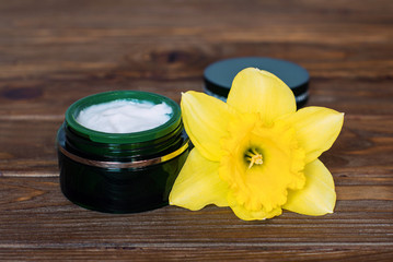 Green jar of cream and narcissus on wooden back ground