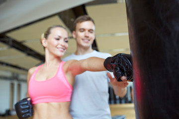 happy woman with personal trainer boxing in gym