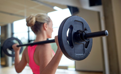 happy woman flexing muscles with barbell in gym