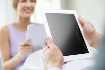 close up of couple with tablet pc at restaurant