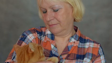 Aged woman stroking a red cat.