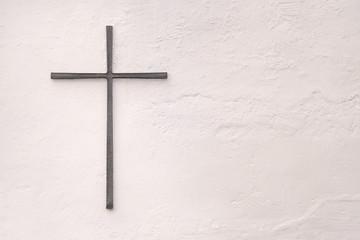 Kreuz aus Metall an einer weissen Wand