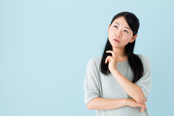 young asian woman thinking on blue background