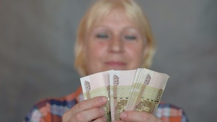Aged woman counting money. Selective focus on money.