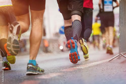 Leinwandbild Motiv Unrecognizable young runners at the city race