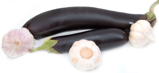 Eggplant on a white background with heads of garlic