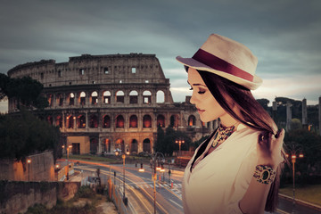 Young woman facing the Colosseum in Rome