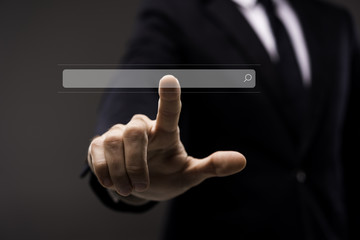 Business man touching imaginery screen with search button