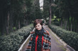 Pretty young woman in a fashion coat walking in a park