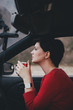 Pretty young woman drinking tea in a car with rain outside