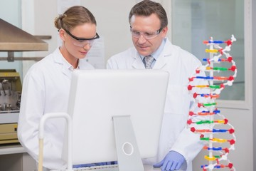 Scientists working on laptop together