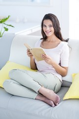 Smiling brunette reading a book on the couch