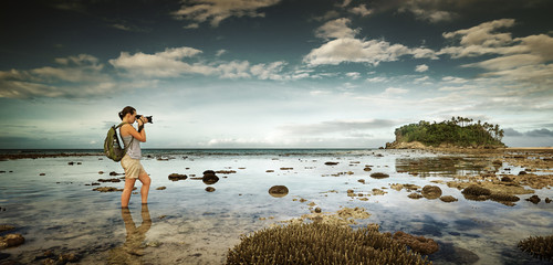 standing in water traveler woman with backpack taking landscape