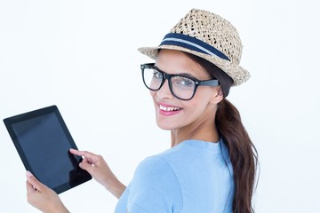 Smiling woman using her tablet looking at camera