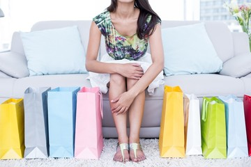 Brunette sitting on the couch with shopping bags around her