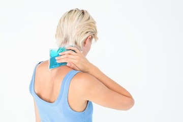Blonde woman putting gel pack on neck