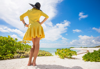 Young woman in yellow dress standing on the beach