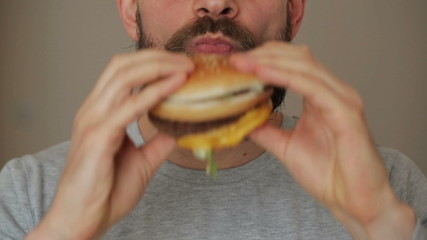 Beared man eats a hamburger
