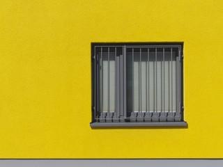 Grauer Fensterrahmen mit Eisengitter in gelber Fassade