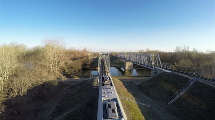 Passenger train goes over the bridge, filming from the top