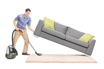 Man lifting a sofa and vacuuming underneath it