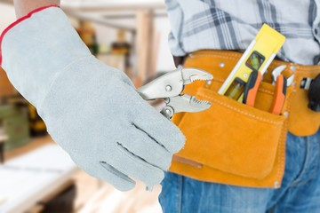 Composite image of technician using pliers over white background